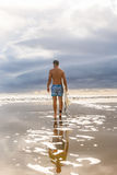 Handsome man with surfing board on spot. Royalty Free Stock Image