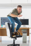 Handsome man surfing his office chair Royalty Free Stock Images