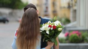 Handsome man surprising lovely woman with flowers stock video footage
