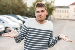 Handsome man in a sweater shrugs. disagreement stock photography