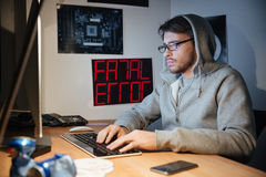Handsome man in sweatshirt with hood typing on computer keyboard Stock Photos