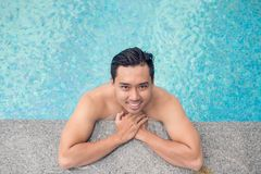 Handsome man in the swimming pool. Portrait of handsome Vietnamese man relaxing in the swimming pool, view from above Stock Image