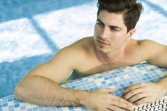 Handsome man in the swimming pool Stock Photos