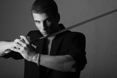 Handsome man with sword. Half body portrait of handsome young man posing with sword, black and white studio background Royalty Free Stock Photos