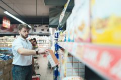 A handsome man takes a batch of flakes from the store shelf. A family man buys food in a supermarket. Stock Photo