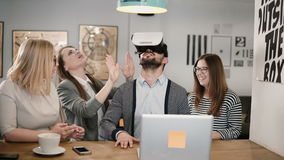 Handsome man takes off glasses virtual reality after using new app share experiences with team in the startup office. Young people try VR helmet in a modern stock video