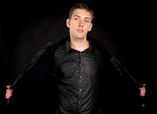Handsome man takes off his jacket. Handsome man takes off his (open) jacket over black background Stock Photo