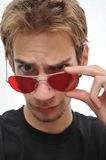 Handsome man taking aviator sunglasses off. Portrait of a young man with red aviator sunglasses Stock Photos