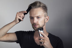 Handsome man taking care of himself. Man combing his hair and shaving his beard stock photo