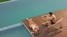 Handsome man taking mobile photo of sunbathing woman. Smiling boyfriend taking picture of girlfriend on poolside. Female model sunbathing near luxury pool stock video