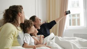 Handsome Man is Taking a Photo by His Smartphone. Positive Family Selfie with Mother, Father and Two Children Lying on. The Bed and Wearing Pajamas, HD stock video footage