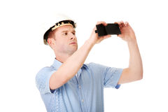 Handsome man taking photos by his mobile phone Royalty Free Stock Photography