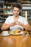 Handsome man taking a picture of his food Royalty Free Stock Images