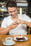 Handsome man taking a picture of his food Royalty Free Stock Photos