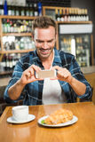 Handsome man taking a picture of his sandwich Royalty Free Stock Image