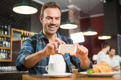 Handsome man taking a picture of his sandwich Stock Photo