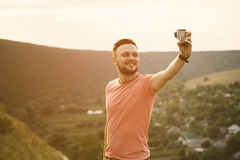 Handsome man taking pictures of him self with action camera Royalty Free Stock Images
