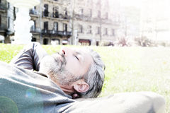 Handsome man taking a rest in public park. Mature man having a nap in city park Royalty Free Stock Image