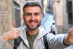 Handsome man taking a selfie and giving a thumbs up. Outdoors Royalty Free Stock Photography