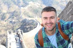 Handsome man taking a selfie in The Great Wall of China.  stock photo