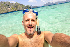 Handsome man taking a selfie during islands hopping at El Nido Stock Images