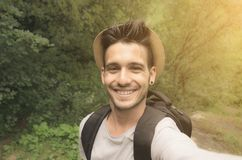 Handsome man taking a selfie on vacation in summertime. Handsome caucasian man is taking a selfie on vacation smiling at the camera on a nature background royalty free stock images