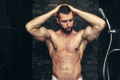 Handsome man taking a shower in the morning. Natural looking athlete showering. Fitness handsome man taking a shower in the morning. Natural looking athlete Stock Photography