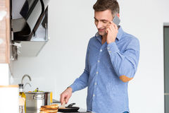 Handsome man talking on cell phone and frying pancakes Royalty Free Stock Photography