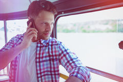 Handsome man talking on mobile phone in bus Stock Photo