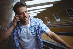 Handsome man talking on mobile phone on escalator Royalty Free Stock Images