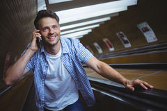Handsome man talking on mobile phone on escalator Royalty Free Stock Photo