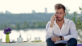 Handsome man talking on the phone outdoors stock footage