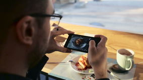 Handsome man talking photo of meal with cellphone sitting in cafe stock video footage