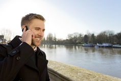 Handsome man talking and smiling on his mobile cell phone Royalty Free Stock Image