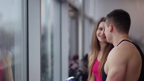Handsome man is talking to a pretty sporty girl near the window. People are resting after workout in the gym stock footage