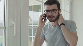 Shocked guy talks on phone near window. Handsome man talks on phone near the window at home. Young guy wearing eyeglasses has a conversation at home at the stock footage