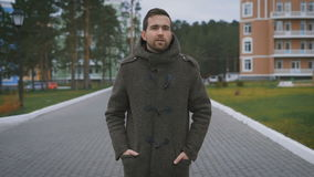 A handsome man, tall walking along a path near the house. He wore a gray coat and black pants. Behind his colorful stock video