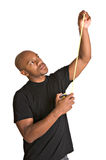 Handsome man with tape measure. Handsome African-American repairman measures with tape measure stock photos