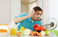 Handsome man tasting veggie soup with ladle Stock Photos