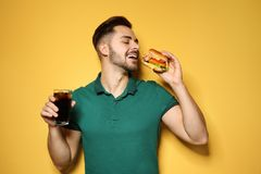 Handsome man with tasty burger and cola stock image
