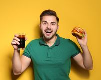 Handsome man with tasty burger and cola stock photo