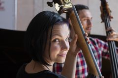 Handsome man teaches how to play double-bass to a beautiful woman royalty free stock photo