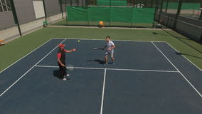 Handsome man teaches the other man play tennis stock video footage