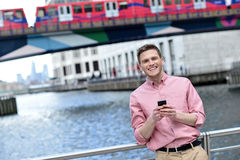 Handsome man texting on a mobile phone. Young man texting through mobile phone at bridge railing Stock Photography