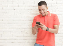 Handsome man texting on mobilephone. Portrait of handsome man texting on mobilephone with copy space on white brick wall background Royalty Free Stock Photo