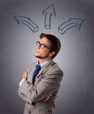 Handsome man thinking with arrows overhead Royalty Free Stock Images