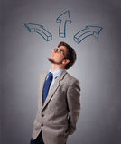 Handsome man thinking with arrows overhead. Handsome young man thinking with arrows overhead Stock Photos