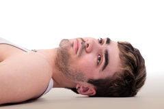 handsome  man thinking lying on floor Stock Photos