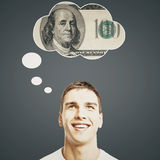 Handsome man thinking about money. Handsome young man thinking about money on dark grey background stock image