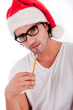Handsome man thinking by wearing santa's hat Royalty Free Stock Images